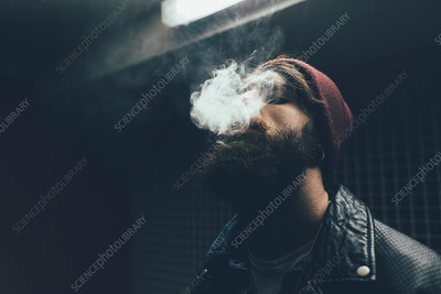 Young male hipster in knit hat smoking at night