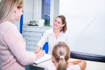 Mother and daughter talking to receptionist