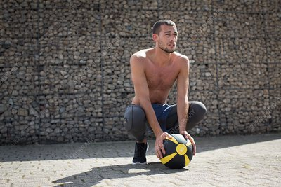 Young man crouching with medicine ball