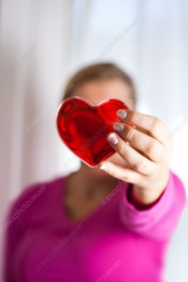 Woman holding red heart in front of her face