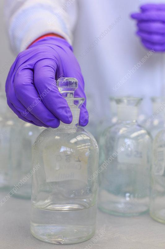 Chemist holding reagent bottle