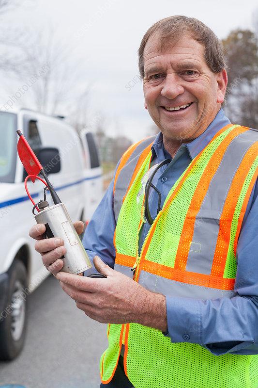 Water department technician holding leak sensor