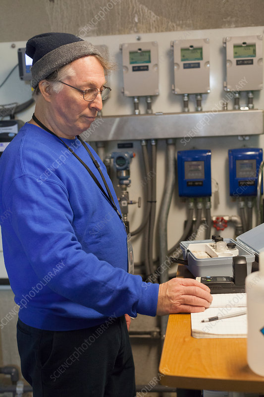 Water treatment engineer recording data