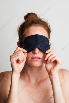 Woman covering her eyes with sleeping mask