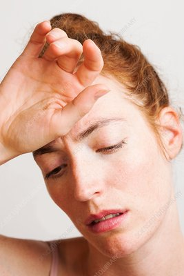 Woman touching her forehead with hand