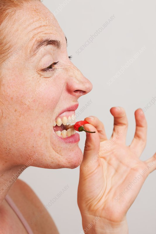 Woman biting into red chili