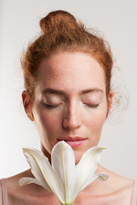 Woman smelling white lily with eyes closed