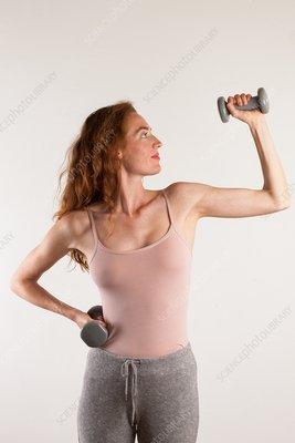 Woman flexing her arm with dumb bells
