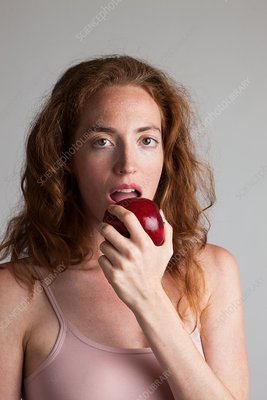 Portrait of woman eating red apple
