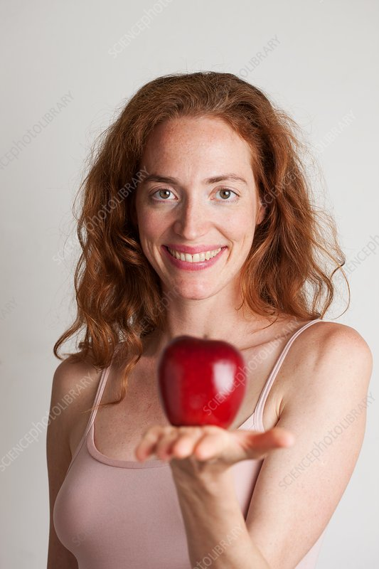 Portrait of smiling woman holding red apple