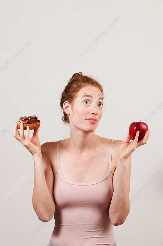 Portrait of woman holding apple and doughnut