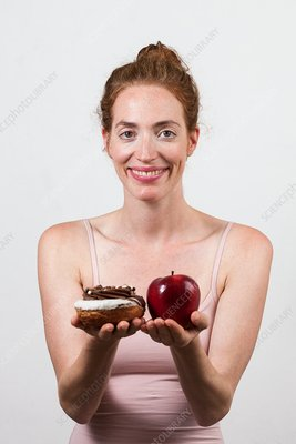 Smiling woman holding apple and doughnut