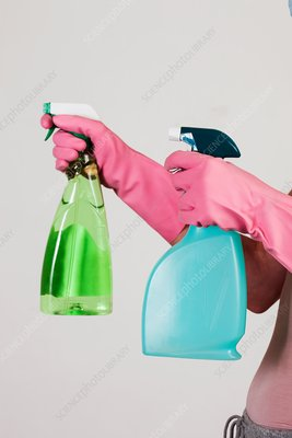 Hands with gloves holding cleaning materials