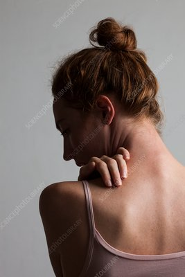 Woman touching her neck and back