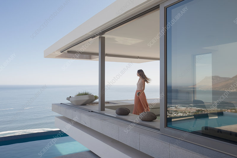 Woman looking at ocean view on balcony