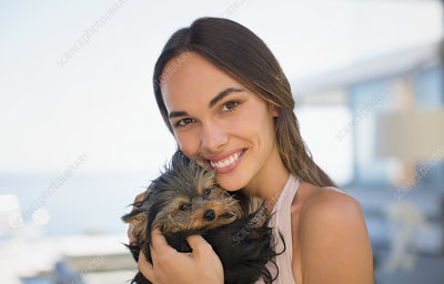 Smiling woman cuddling small dog
