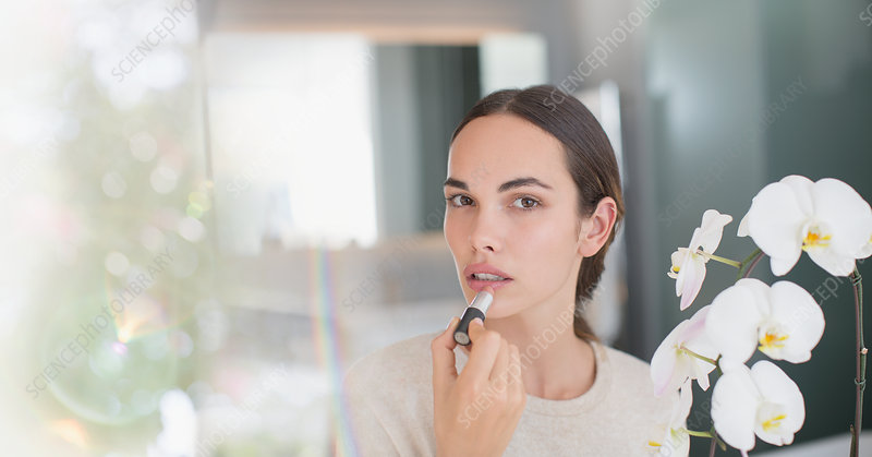 Brunette woman applying lipstick