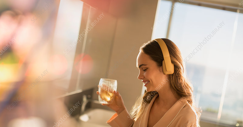 Smiling woman listening to music and drinking