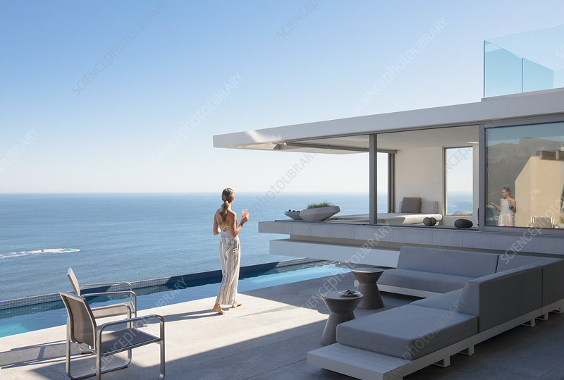 Woman on sunny modern home exterior patio
