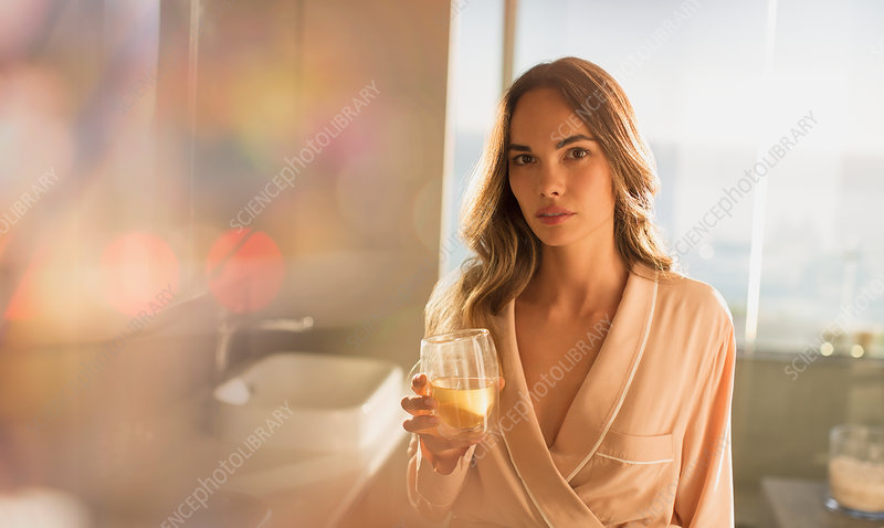 Serious woman in bathrobe drinking