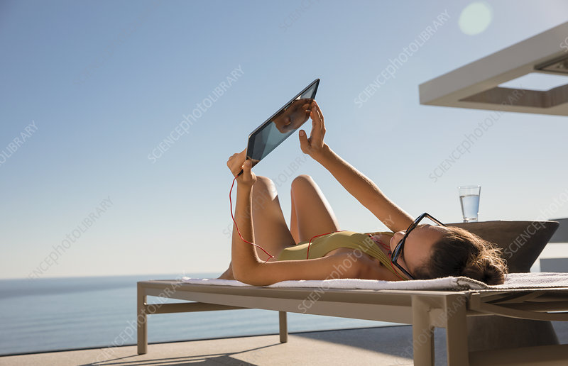 Woman sunbathing, using digital tablet