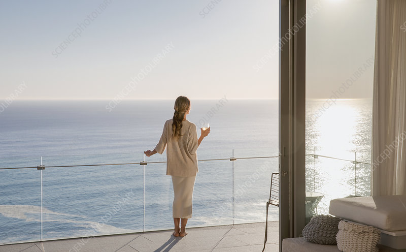 Woman standing on sunny balcony