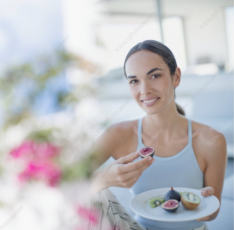 Woman eating figs and kiwi