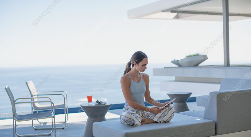 Woman using digital tablet on patio