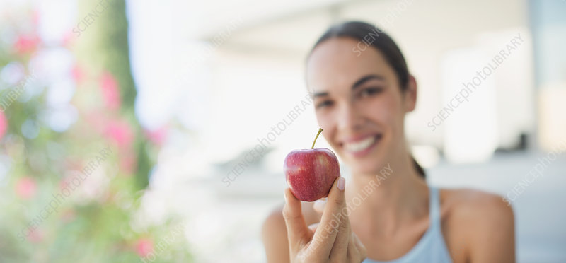 Smiling brunette woman holding red apple