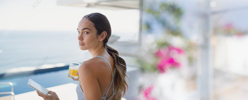Brunette woman drinking orange juice on patio