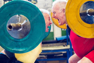 Two senior powerlifters face to face, shouting