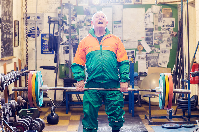 Senior male powerlifter struggling to lift barbell in gym