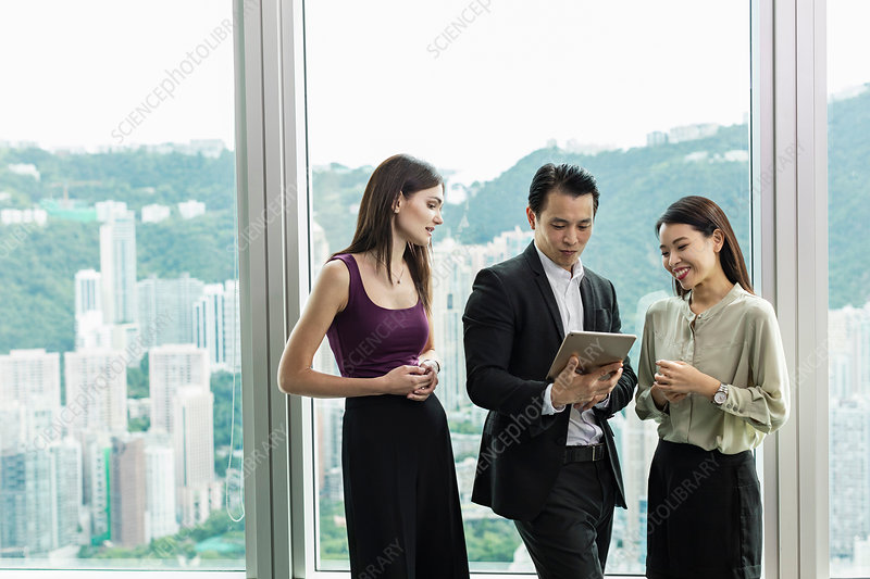 Colleagues with digital tablet standing chatting