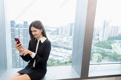 Woman sitting on windowsill using smartphone