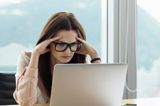Woman using laptop, head in hands looking stressed