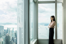 Business woman looking out of window at cityscape