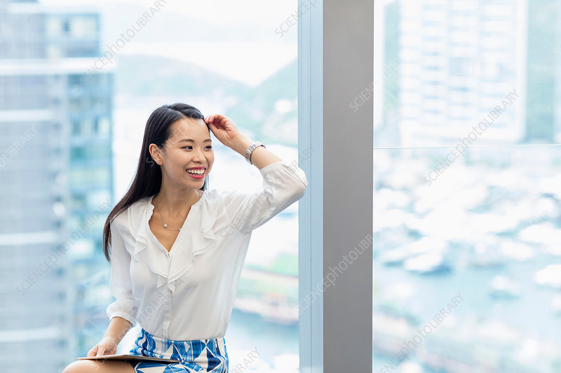 Woman with digital tablet looking away smiling