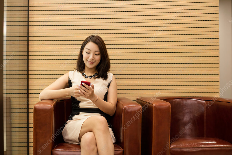 Business woman sitting in leather chair using smartphone