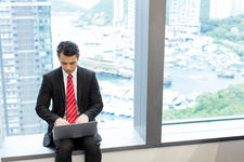 Businessman sitting on windowsill using laptop