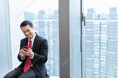 Businessman sitting on windowsill using smartphone smiling