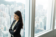 Businesswoman, arms crossed, looking out of window