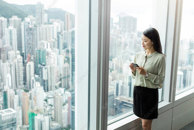 Businesswoman with smartphone looking out of window