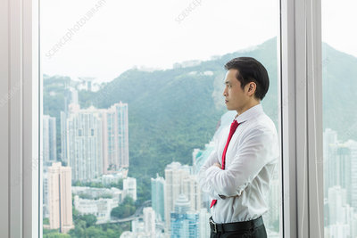Businessman, arms folded looking out of window