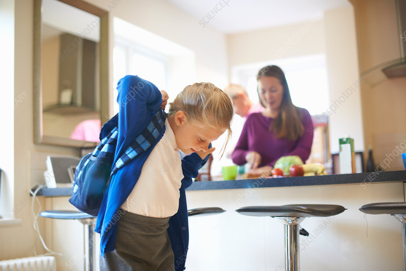 Schoolgirl putting on school satchel in kitchen