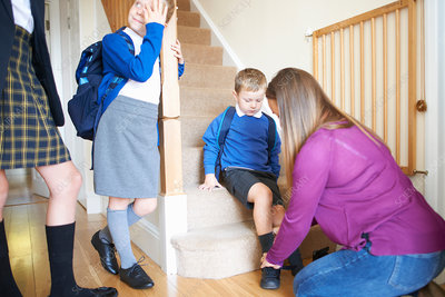 Woman putting on son's school shoe on stairs