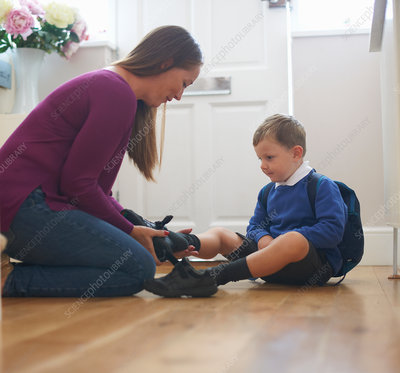 Woman putting on son's school shoe in hallway