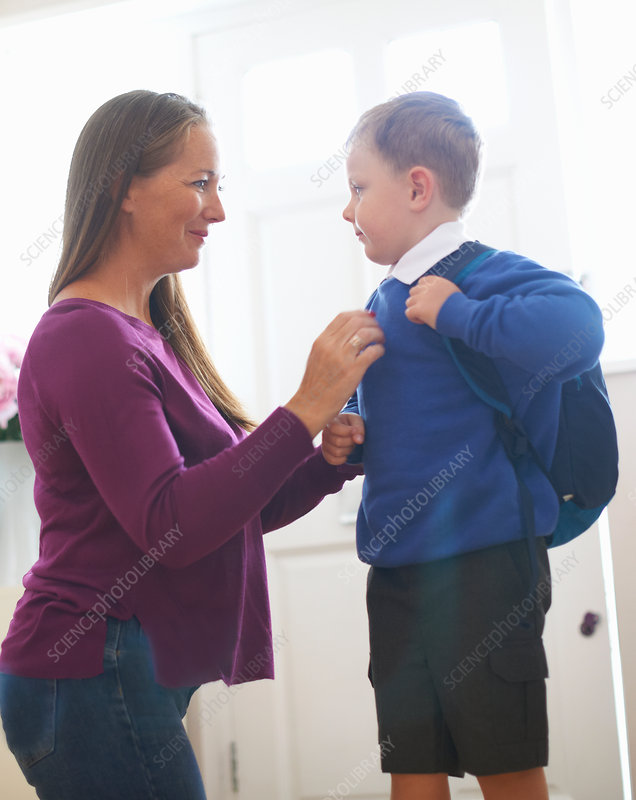 Woman adjusting son's school sweater in hallway