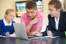 Father helping daughters with homework at kitchen counter