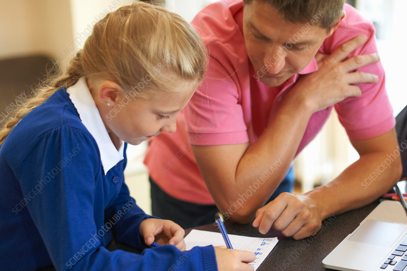 Father helping daughter with homework at kitchen counter