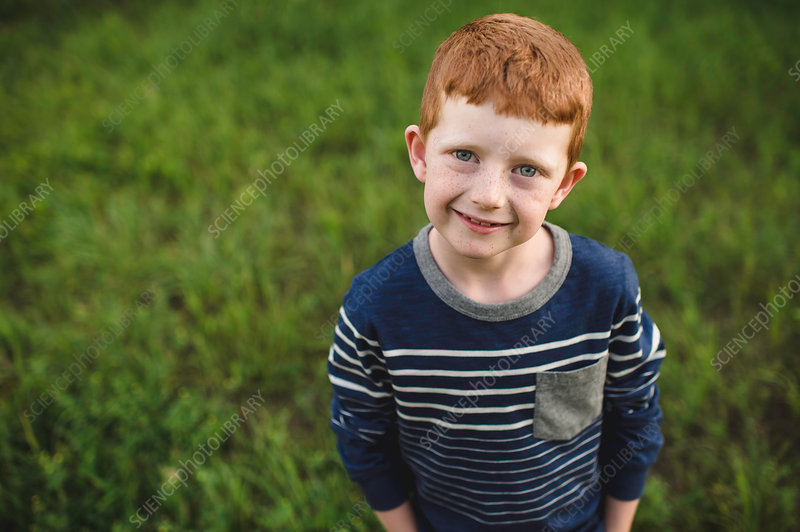 Portrait of red haired boy standing on grass